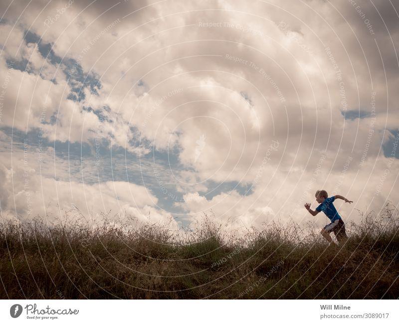 Ein Junge rennt über den Gipfel eines Hügels. rennen Laufsport Läufer Wolken Himmel sehr wenige Textfreiraum üben Jugendliche Junger Mann Jugendkultur Kind Gras