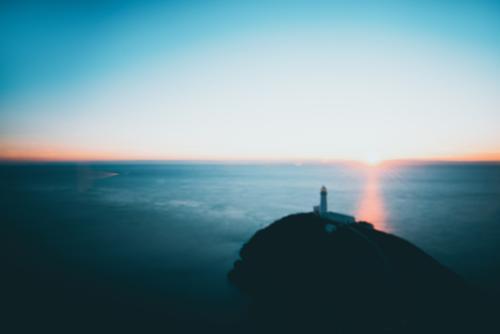 verträumt - ein Leuchtturm und die untergehende Sonne am Horizont starke Tiefenschärfe Unschärfe unscharf verschwommener hintergrund Träumen Traum Meer Ozean