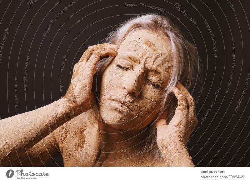Frau, die mit trockener, gerissener Tonschlammmaske bedeckt ist, die ihren Kopf hält. schön Haut Gesicht Gesundheit Krankheit Wellness Mensch Junge Frau