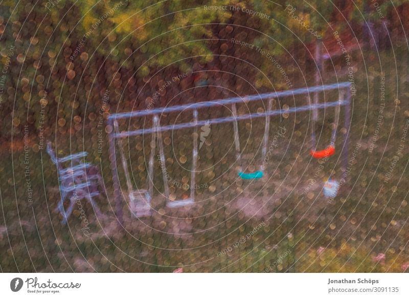 Blick auf einen Garten mit Schaukeln durch ein Fliegengitter Herbst mehrfarbig Gitter Außenaufnahme Spielplatz Schirmtür Fenster Insektenschutz Wiese Haus