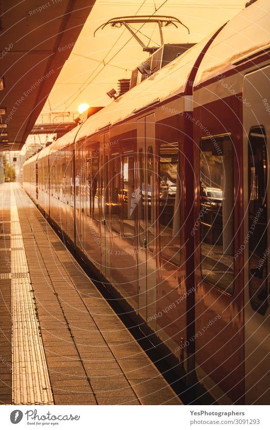 Die Fahrgäste fahren zur goldenen Stunde am Bahnhof. Ferien & Urlaub & Reisen Ausflug Verkehr Verkehrsmittel Personenverkehr Öffentlicher Personennahverkehr