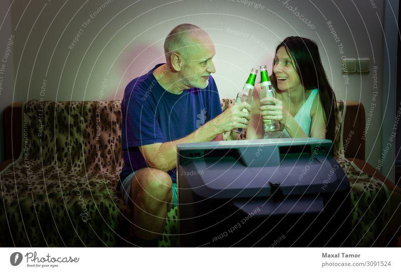 Ein erwachsener Mann und eine erwachsene Frau schauen sich Sport im Fernsehen an. trinken Alkohol Bier Lifestyle Freude Glück Gesicht Erholung Freizeit & Hobby