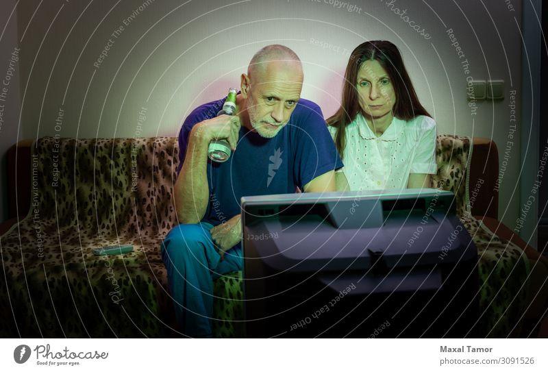 Mann und Frau mittleren Alters, schauen fern, sehen traurig aus. trinken Alkohol Bier Lifestyle Gesicht Erholung Freizeit & Hobby Sofa Entertainment Publikum