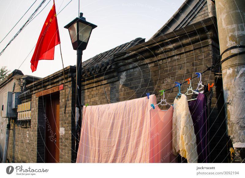 Waschtag in Peking Chinesische Architektur Mauer Eingangstor Wäsche Wäscheleine Fahne Straßenbeleuchtung Kleiderbügel Backstein hängen authentisch Tatkraft