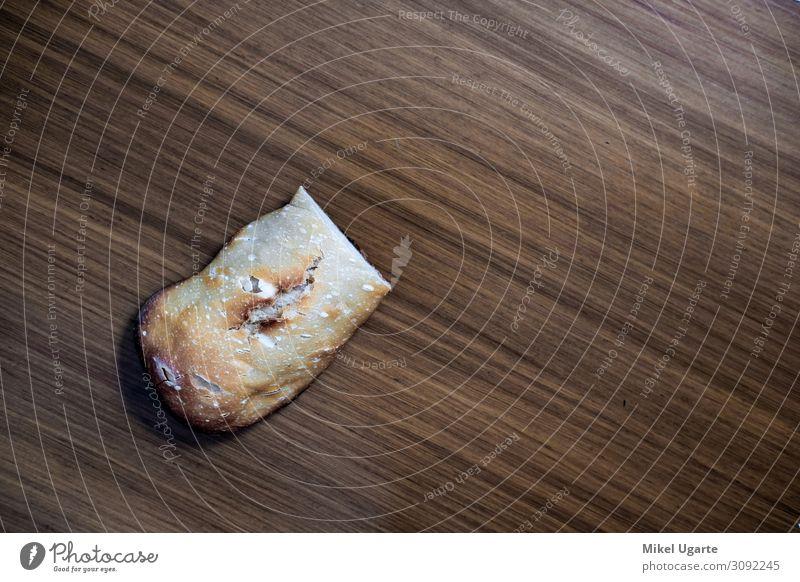 Ein Stück hausgemachtes Brot über dem Küchentisch Lebensmittel Teigwaren Backwaren Ernährung Frühstück Mittagessen Abendessen Tisch Holz dunkel frisch heiß