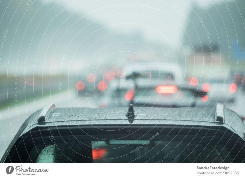A car is driving on the road in the rain Ferien & Urlaub & Reisen Umwelt Wetter schlechtes Wetter Verkehr Autofahren Straße Autobahn PKW