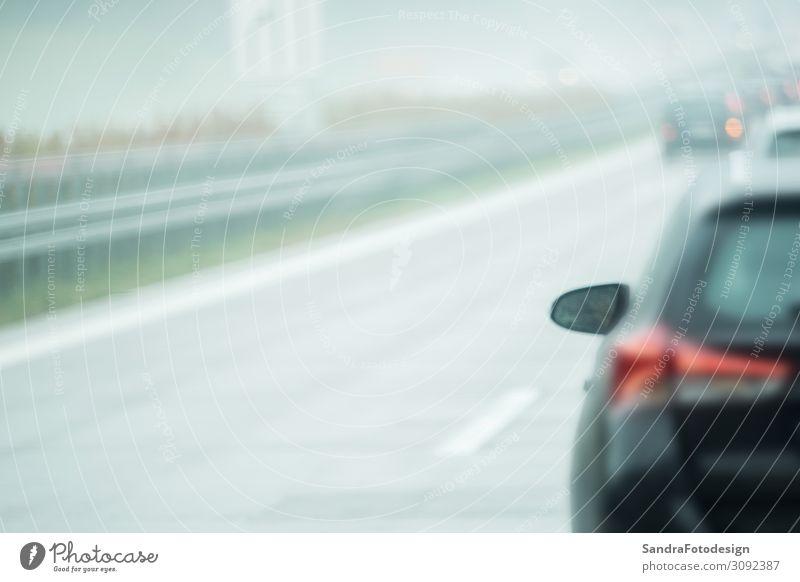 A car is driving on the road in the rain Ferien & Urlaub & Reisen Arbeit & Erwerbstätigkeit Umwelt schlechtes Wetter Verkehr Verkehrsmittel Straße Autobahn PKW