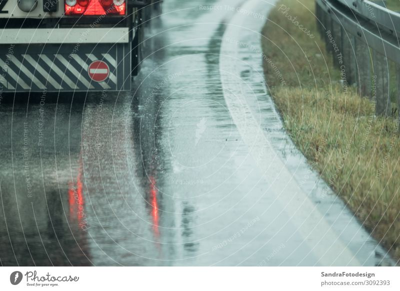 A truck is driving on the road in the rain Arbeit & Erwerbstätigkeit Güterverkehr & Logistik Dienstleistungsgewerbe Wetter Regen Verkehr Straße Autobahn