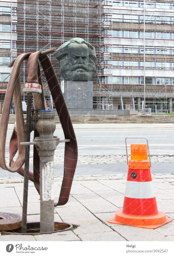 Hydrant mit Wasserschlauch und Absperrkegel mit Warnleuchte steht am Straßenrand, im Hintergrund das Karl-Marx-Denkmal vor einer Häuserfassade in Chemnitz Stadt