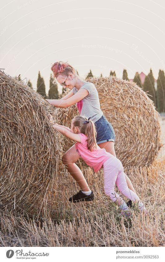 Schwestern, die Heuballen schieben und auf dem Land zusammen spielen. Lifestyle Freude Glück Erholung Freizeit & Hobby Ferien & Urlaub & Reisen Freiheit Sommer