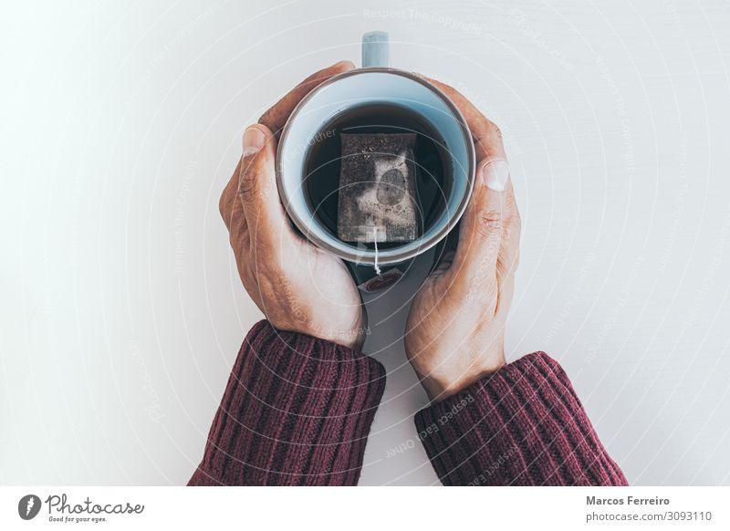 Teetasse zwischen den Händen Becher Erholung Winter Häusliches Leben Schreibtisch Tisch trinken Mensch maskulin Jugendliche Hand Finger 1 30-45 Jahre Erwachsene