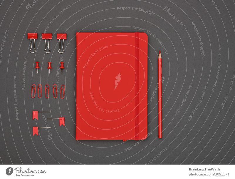 Ordentlich organisiertes rotes Briefpapier flach auf grau gelegt Schreibtisch Tisch Arbeitsplatz Büro Schreibwaren Papier dunkel modern oben schwarz Farbe