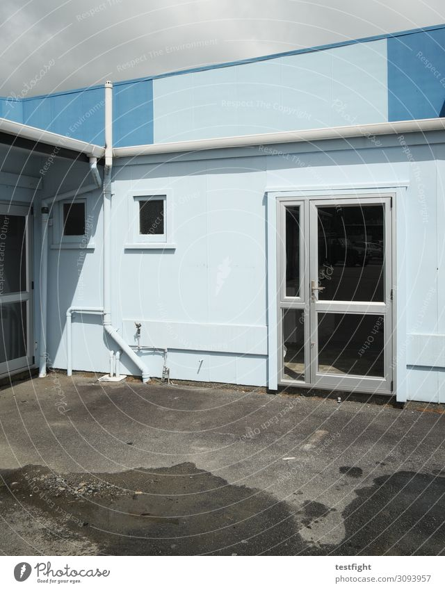 hintereingang Sonne Klima Regen Kleinstadt Stadt Stadtrand Menschenleer Haus Bauwerk Gebäude Architektur Mauer Wand Fassade Tür alt geschlossen blau Büro Röhren