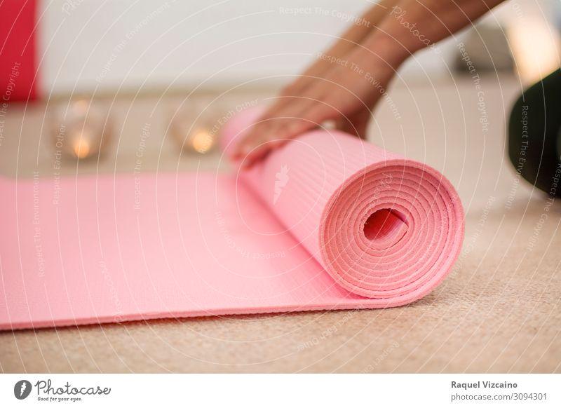 Frauenhände wickeln die rosa Yogamatte auf. Lifestyle Wellness Erholung Meditation Sport Hand Kerze atmen Gesundheit braun friedlich ruhig Zufriedenheit