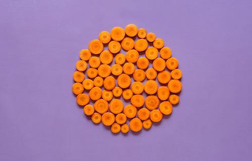 Geschnittene Karotten im Kreis auf violettem Hintergrund Gemüse Ernährung Vegetarische Ernährung Diät Gesunde Ernährung Winter Herbst frisch Gesundheit