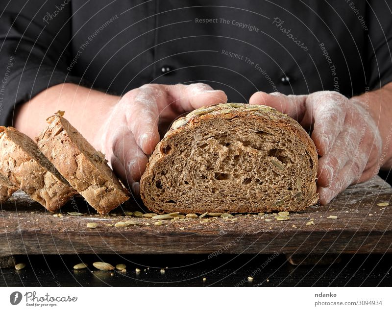 Koch in schwarzer Uniform schneidet ein Stück Brot ab. Ernährung Essen Mittagessen Abendessen Tisch Küche Mann Erwachsene Hand Holz dunkel frisch lecker