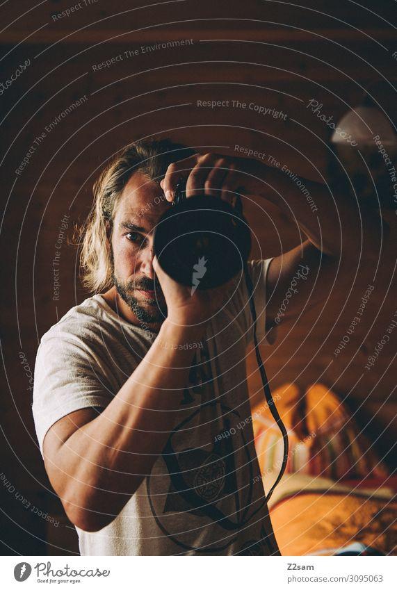 Der Fotograf Lifestyle Wohnung Spiegelreflexkamera Objektiv Junger Mann Jugendliche 30-45 Jahre Erwachsene T-Shirt blond langhaarig Bart festhalten Coolness