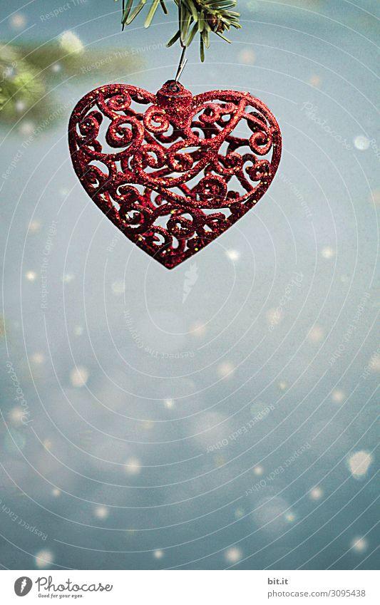 Roter, filligrner Weihnachtsschmuck als Herz mit orientalischem Muster, hängt im Schneefall an Tannenzweig. Christbaumanhänger in Herzform aufgehängt an Christbaumzweig mit Schneeflocken. Schöne, fröhliche, geschwungene Weihnachtsdekoration und Verzierung.