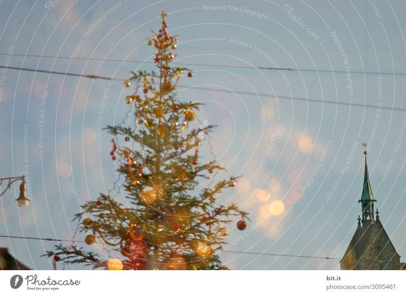 Kitschiger, skurriler, geschmückter Weihnachtsbaum steht zwischen Leitungen, Kirche, Lampe und Laterne in der Stadt und leuchtet. Lustige, abstrakte, leuchtende, witzige, urbane Weihnachtsstimmung mit Christbaum & Licht draussen vor blauem Himmel im Advent