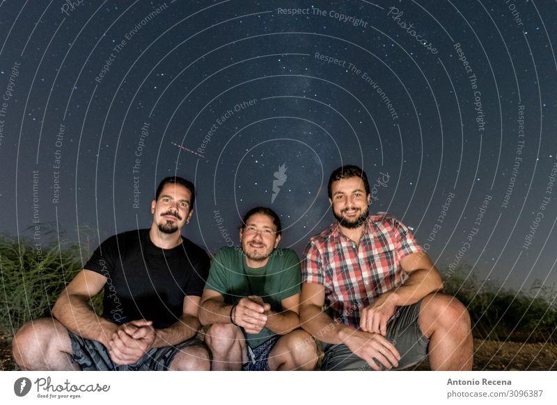 drei Freunde, die mit der Milchstraße im Hintergrund posieren. Lifestyle Glück Erholung Sommer Mensch Mann Erwachsene Freundschaft Himmel sitzen Coolness dunkel