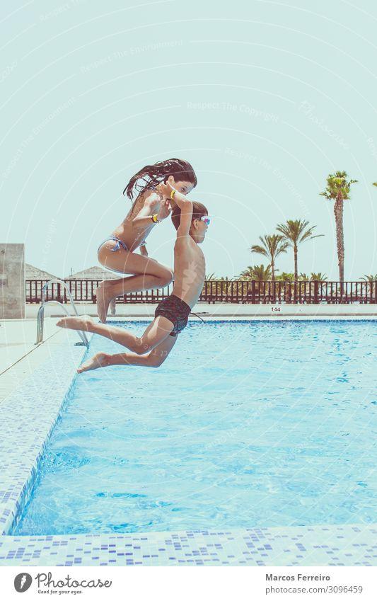 Kinder, die in den Pool springen. Lifestyle Leben Sommerurlaub Sonne Wassersport Schwimmen & Baden Schwimmbad Mensch Mädchen Junge Körper 2 3-8 Jahre Kindheit