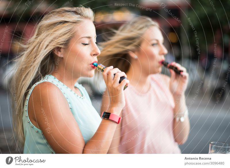 zwei blonde Schwestern mit E-Zigarren-Rauchen auf der Bar-Terrasse Lifestyle elegant schön Freizeit & Hobby Technik & Technologie Mensch Frau Erwachsene Hand