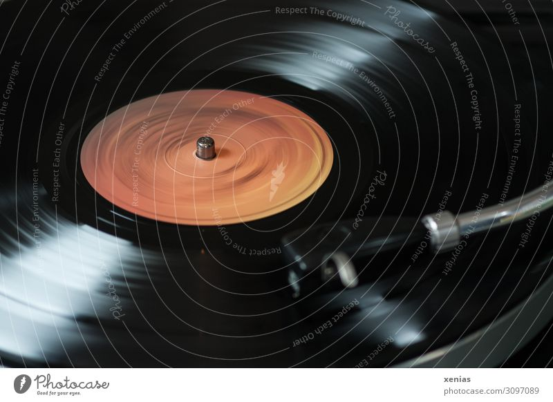 Schallplatte läuft...und läuft Plattenspieler Unterhaltungselektronik Fortschritt Zukunft Musik Medien drehen hören dunkel orange schwarz Vintage Detailaufnahme