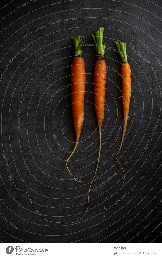 Drei Möhren Lebensmittel Gemüse Bioprodukte Vegetarische Ernährung Diät frisch Gesundheit grün orange schwarz 3 Foodfotografie Farbfoto Studioaufnahme