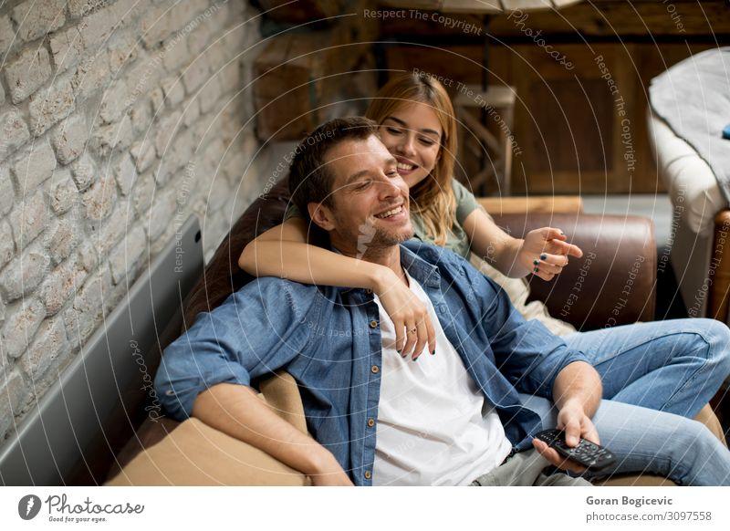 Lächelndes junges Paar zum Entspannen und Fernsehen zu Hause Lifestyle Freude schön Erholung Sofa Technik & Technologie Mensch Frau Erwachsene Mann