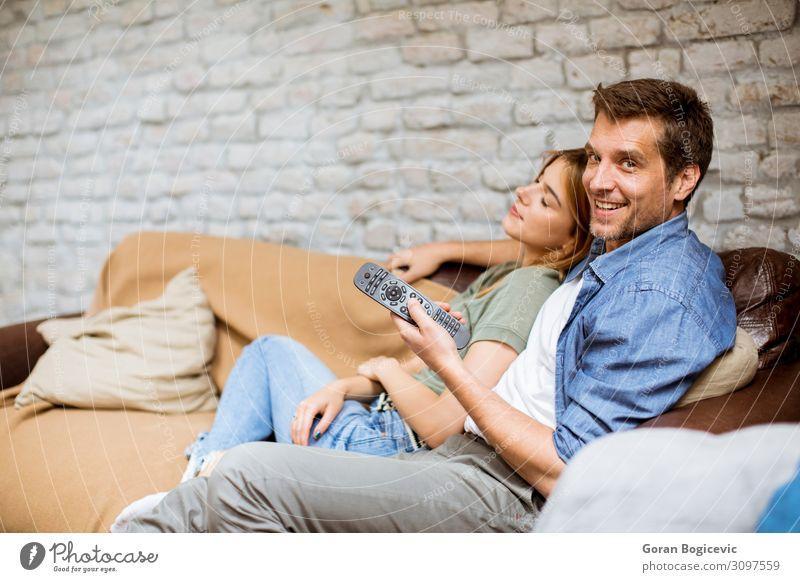 Lächelndes junges Paar zum Entspannen und Fernsehen zu Hause Lifestyle Freude Erholung Wohnung Sofa Technik & Technologie Mensch Frau Erwachsene Mann