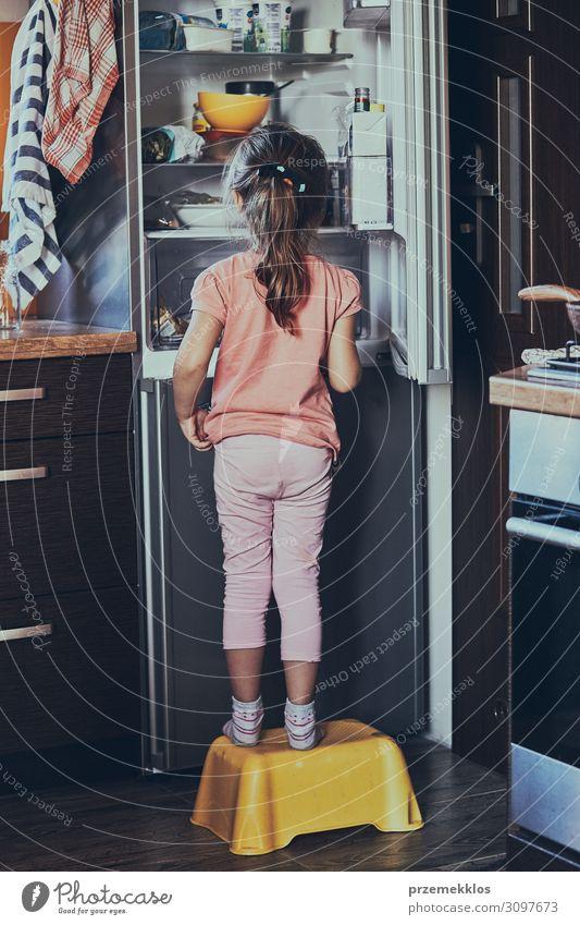 Kleines Mädchen auf einem Kinderhocker vor dem geöffneten Kühlschrank stehen. Lifestyle Küche 1 Mensch 3-8 Jahre Kindheit authentisch gut klein heimwärts Rücken