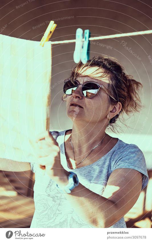 Frau hängend gewaschene Bettwäsche an der Wäscheleine Sommer Erwachsene 1 Mensch 45-60 Jahre Bekleidung Sonnenbrille authentisch nass Sauberkeit erhängen