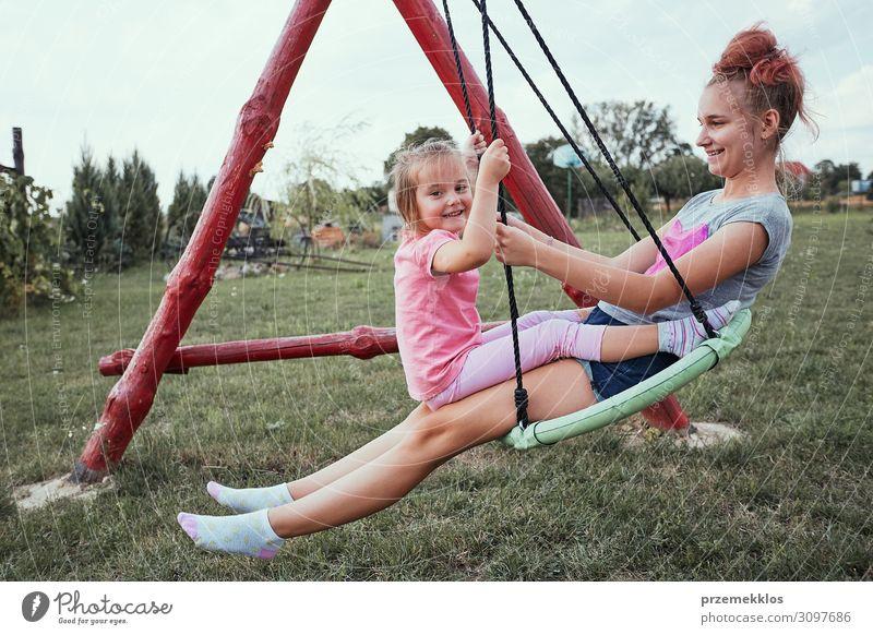 Schwestern beim gemeinsamen Spaß auf einer Schaukel Freude Ferien & Urlaub & Reisen Sommer Sommerurlaub Garten Kind Familie & Verwandtschaft 2 Mensch 3-8 Jahre