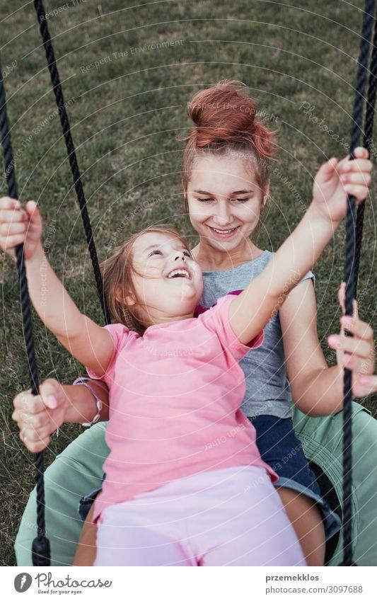 Schwestern beim gemeinsamen Spaß auf einer Schaukel Freude Ferien & Urlaub & Reisen Sommer Sommerurlaub Garten Familie & Verwandtschaft Kindheit 3-8 Jahre