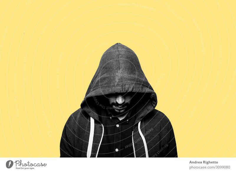 Konzept der Hacker, Cyber-Bedrohungen, Jugenddepressionen, Schwierigkeiten im Jugendalter. Junger kaukasischer männlicher Student, der auf den Boden starrt und dessen Augen von einer Kapuze verdeckt sind. Gelber Hintergrund