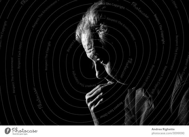 Begriff der Depression. Ein alter Mann, der im Dunkeln in schwarz-weiß mit schwarzem Hintergrund auf nichts starrt. Gesundheitswesen Behandlung Seniorenpflege