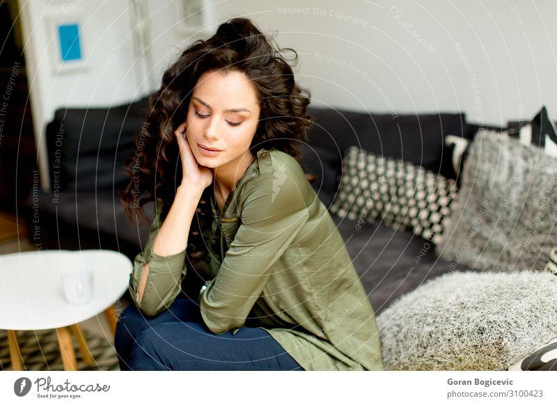 Porträt einer jungen Frau mit lockigem Haar Lifestyle schön Haare & Frisuren Wohnung Haus Sofa Mensch feminin Junge Frau Jugendliche Erwachsene Kopf 1