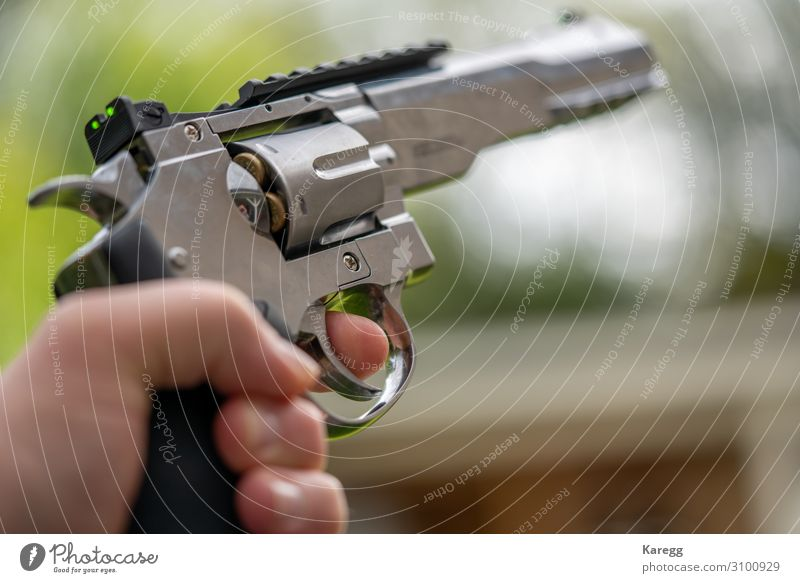 in one hand is large silver heavy revolver and aims into the air Roulette Mensch maskulin Junger Mann Jugendliche Hand 1 8-13 Jahre Kind Kindheit Aggression