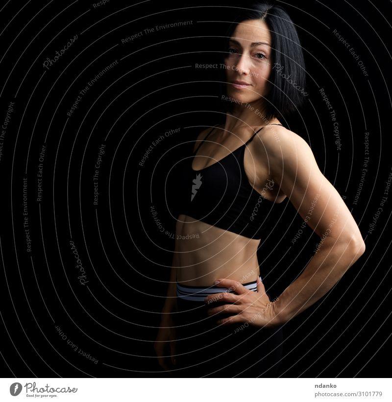 Erwachsenes Mädchen mit einer Sportfigur im schwarzen BH Lifestyle schön Körper Frau Hand Bekleidung brünett Fitness Lächeln stehen sportlich dunkel dünn Erotik