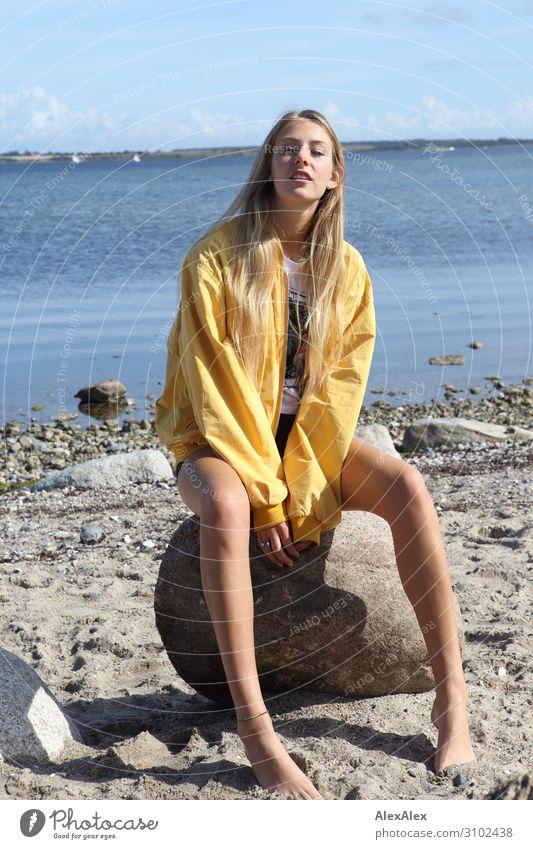 Junge Frau mit gelber Jacke sitzt am Strand Lifestyle Freude schön Leben Sommer Sonne Sonnenbad Meer Jugendliche Beine 18-30 Jahre Erwachsene Schönes Wetter