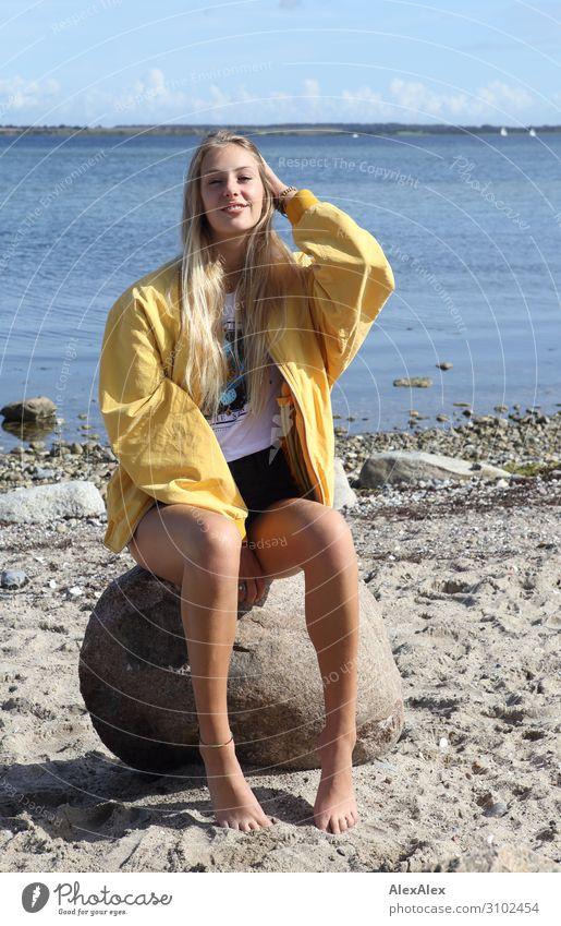 Junge Frau mit gelber Jacke auf einem Fels am Strand Stil Freude schön Leben Wohlgefühl Sommer Sommerurlaub Sonne Meer Jugendliche Beine 18-30 Jahre Erwachsene