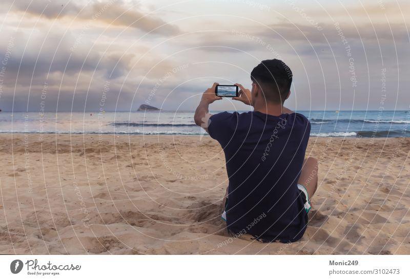 Junge mit Blick auf das Meer, der mit einem Smartphone ein Foto macht. Glück Erholung Ferien & Urlaub & Reisen Tourismus Strand Wellen Telefon Handy