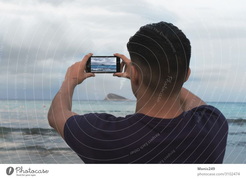 Brünetter Junge mit Blick auf das Meer, der mit einem Smartphone ein Foto macht. Erholung Ferien & Urlaub & Reisen Tourismus Strand Wellen Winter sprechen