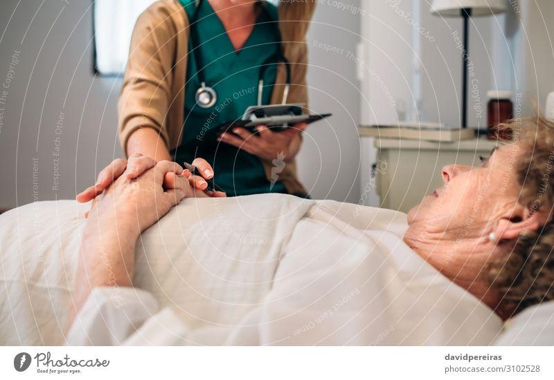 Ärztin tröstet ältere Patientin Krankheit Medikament Haus Arzt Krankenhaus Mensch Frau Erwachsene Hand alt authentisch Freundlichkeit Vertrauen Mitgefühl