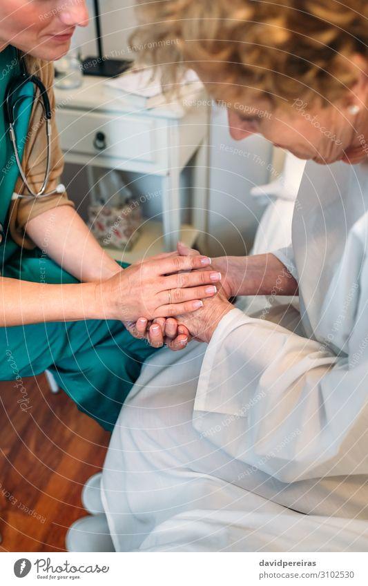 Ärztin hält Hand des Patienten Krankheit Medikament Arzt Krankenhaus sprechen Mensch Frau Erwachsene alt authentisch Freundlichkeit Vertrauen Mitgefühl