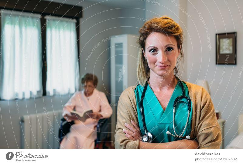 Hübsche Ärztin, die in einer Altersklinik posiert. schön Gesundheitswesen Krankheit Erholung lesen Schlafzimmer Arzt Krankenhaus Mensch Frau Erwachsene alt