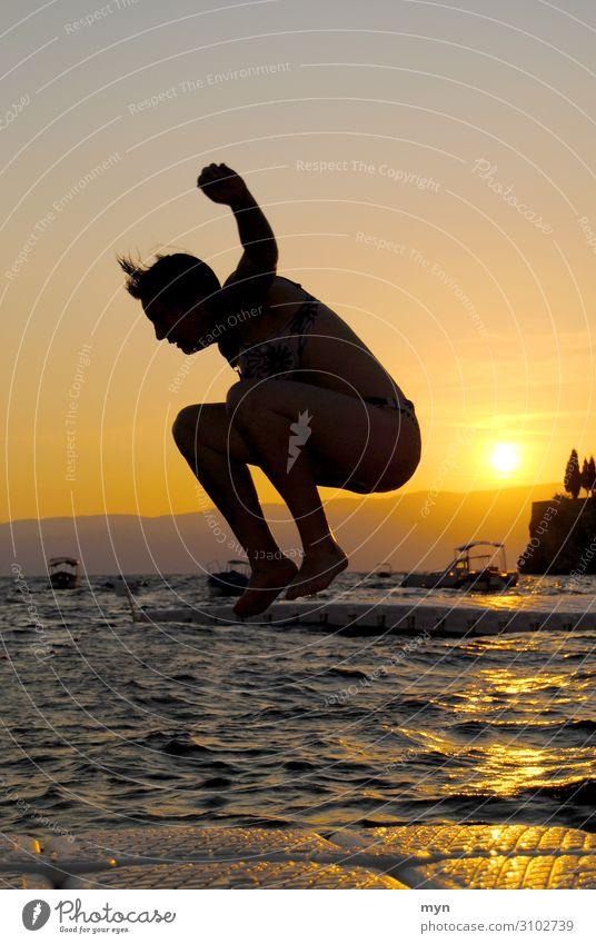 Silhouette von Frau vor Sonnenuntergang, die ins Wasser springt sprung springen See badespaß baden Schwimmen & Baden Sommer Lebensfreude Spaß haben Freude Glück
