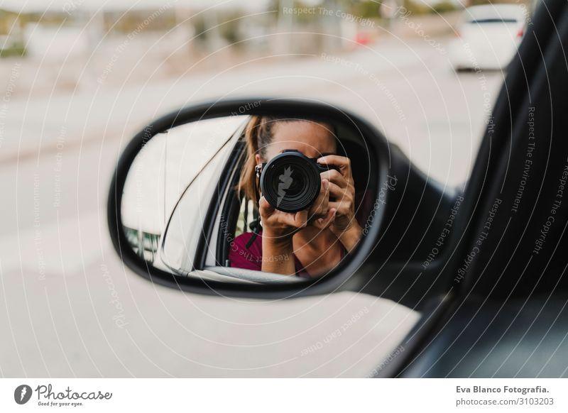 junge Frau, die ein Foto aus dem Rückspiegel eines Autos macht. Reisen und Lebensstil im Freien Freude PKW Ferien & Urlaub & Reisen Verkehr Heck Ausflug