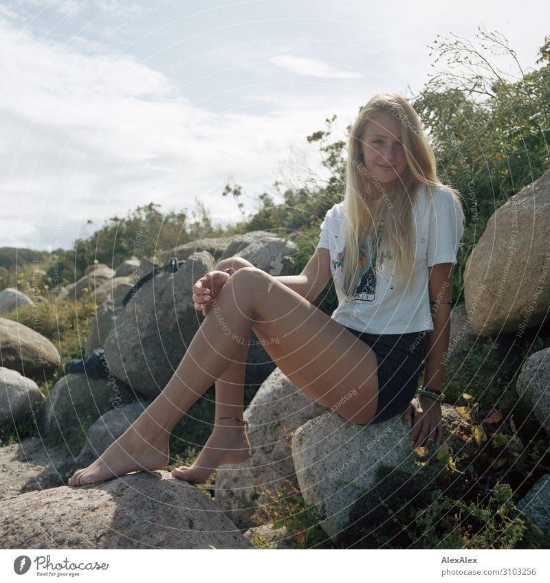 Portrait einer jungen, großen Frau, die auf einer Felsendüne sitzt und lächelt Stil Freude schön Leben Wohlgefühl Sommer Sommerurlaub Strand Junge Frau