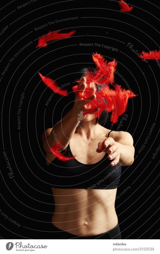 schönes athletisches Mädchen in schwarzer Kleidung wirft rote Federn hoch. Lifestyle Körper sportlich Fitness Sport Mensch Kleinkind Frau Erwachsene Arme stehen